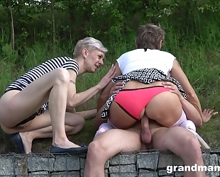 Pair of nasty matures sharing one stiff shaft outdoors