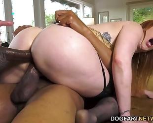 Busty redhead nympho in stockings serves two big black schlongs